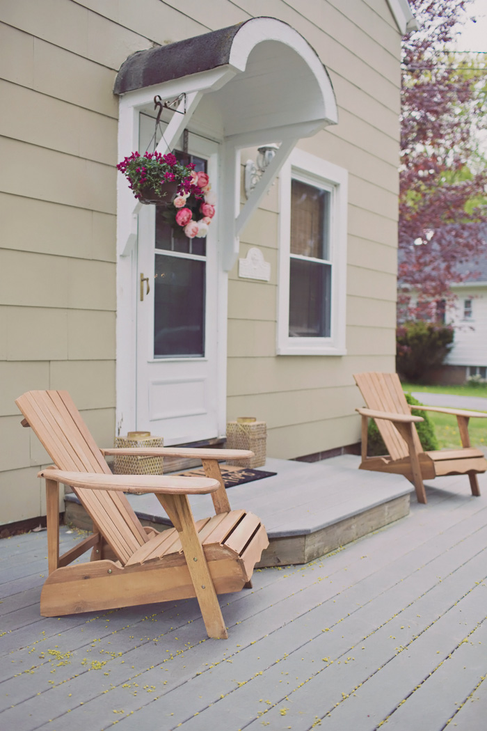 open front porch decorated to sell with chairs, plants and wreath