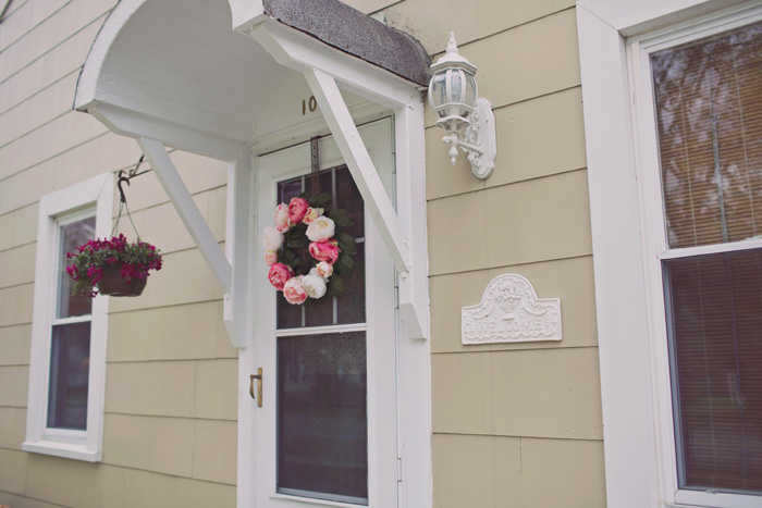 Front door on open porch with white roof overhang and faux peony wreath