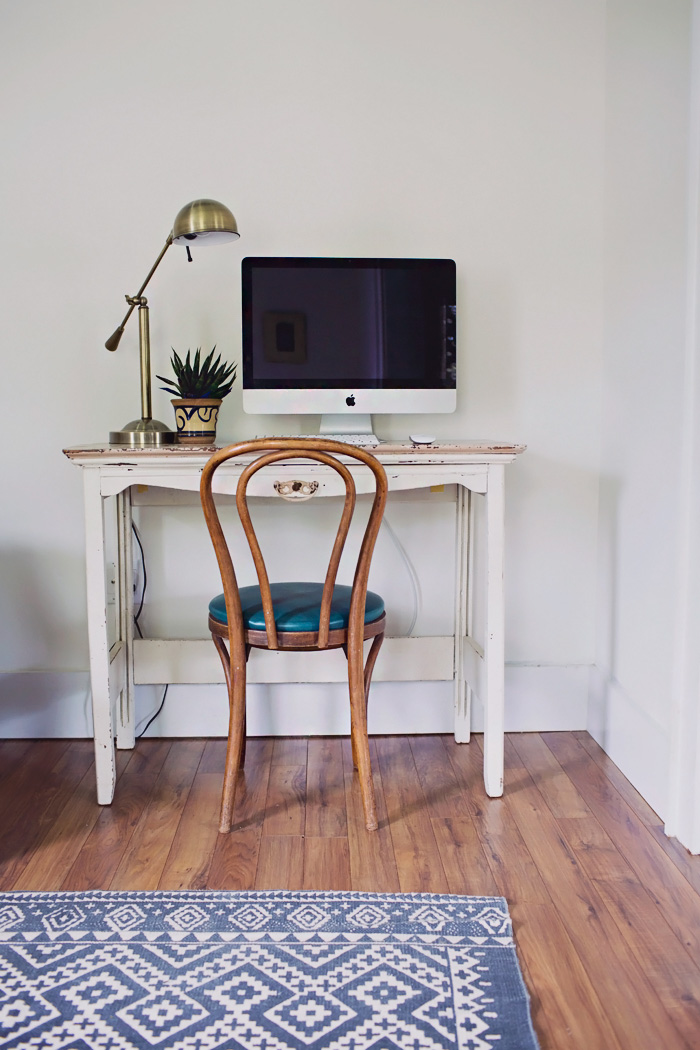 In home office simple minimalist desk area with chair lamp and plant