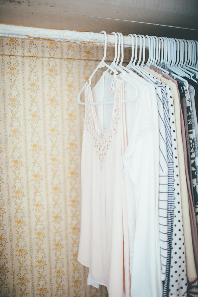 Old Closet with floral wallpaper and neutral clothing organized by color