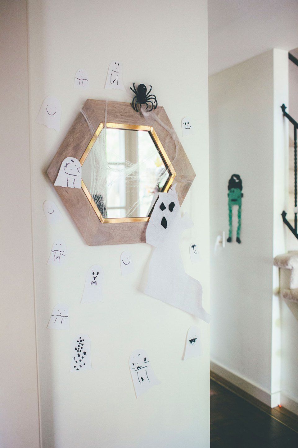 Mirror decorated with paper ghosts and spider webs