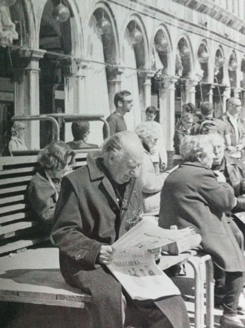 Old man reading the newspaper in St Mark's Square in Venice, Italy.