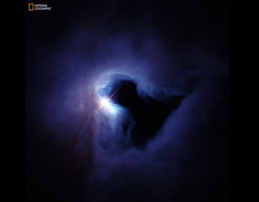 Eerie Fog Like an ominous fog swirling around a street lamp, a nebula 1,499 light-years away in the constellation Orion burns dimly, illuminated by hot, massive stars embedded inside the gas cloud