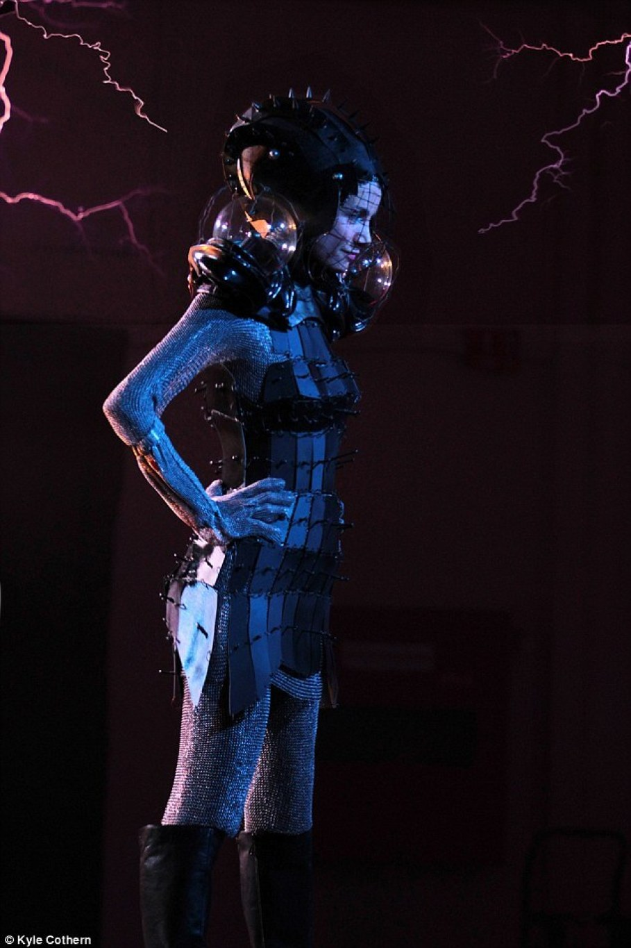 When Ms Wipprecht stood between the coils on stage, the metal in the chainmail dress (pictured) conducted this energy and pushed it towards the ground.The chainmail worked as a Faraday cage - which uses its mesh-like structure to move electrostatic charges and pass them around the outside of the 'cage'