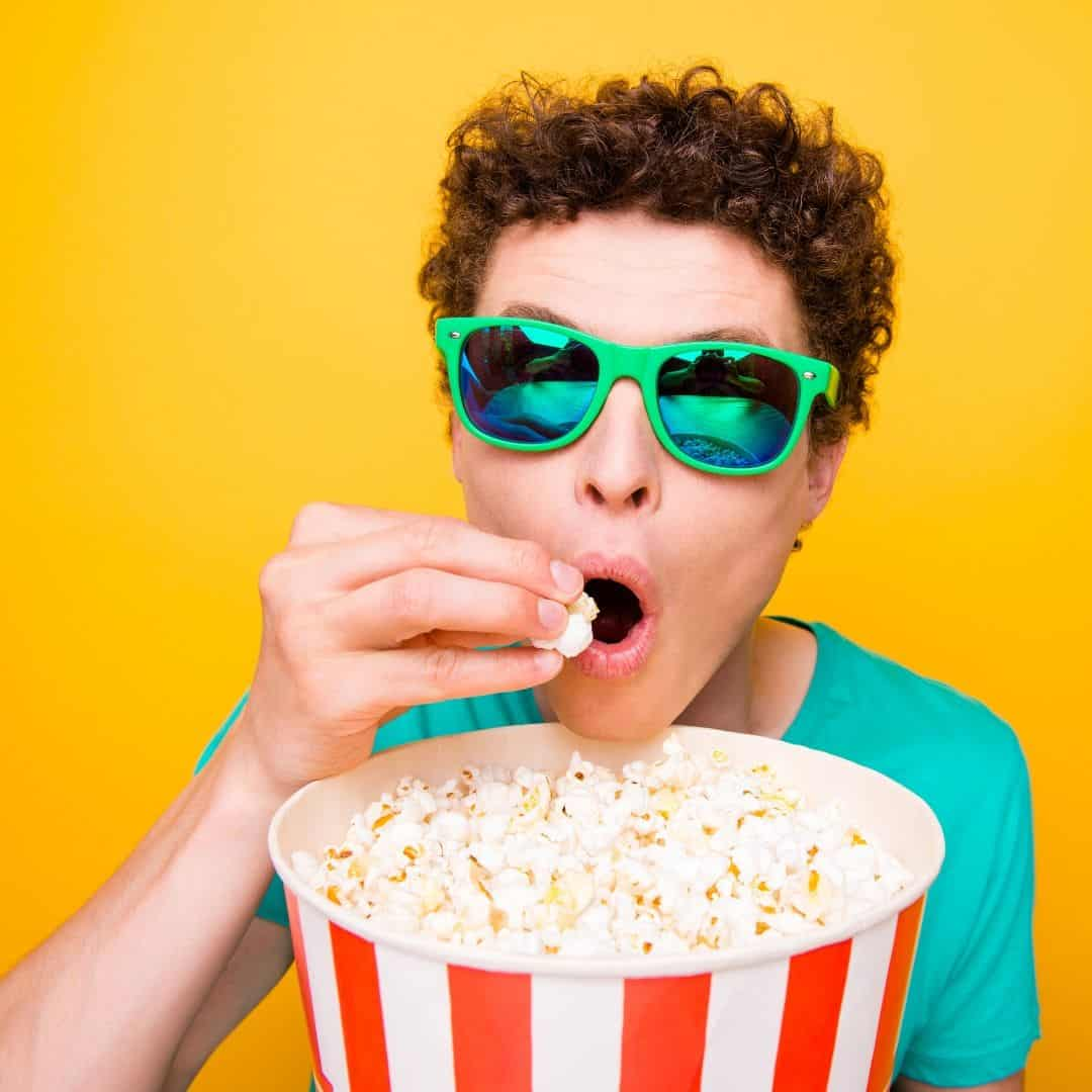 person with bright green glasses on a yellow background eating from a large bucket of popcorn - free cinema tickets for carers