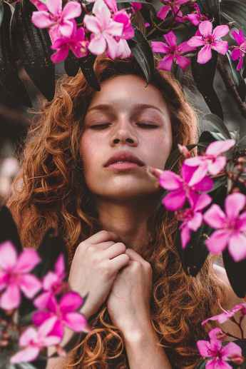 woman surrounded by pink petaled flowers