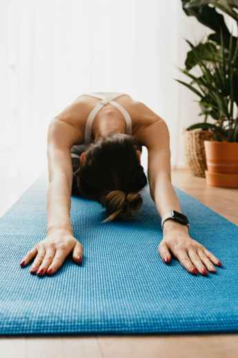 flexible faceless woman lying in child pose on yoga mat
