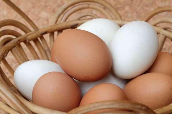 Huevos marrones y huevos blancos en una canasta