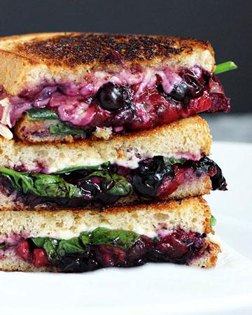 Sándwich con queso asado, arándanos y fresas.