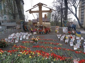 Flowers, candles, cross and portraits of killed people at Institutskaya street