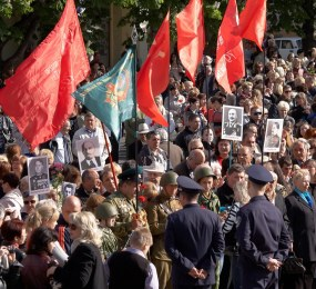 People at parade hold portraits of Lenin, Stalin and soviet generals