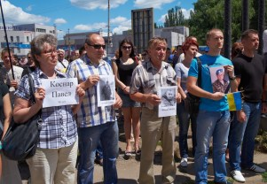 People hold sheets with names of died paratroopers