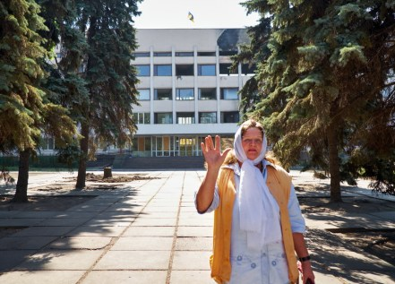 Woman in front of ruined City Hall of Mariupol