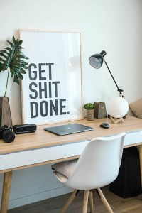 Desk with laptop and big sign saying Get Shit Done on it.
