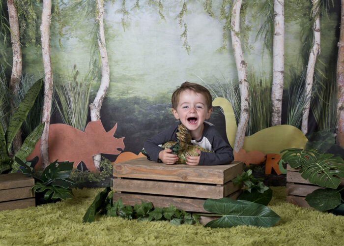 young boy photoshoot with dinosaur background and props