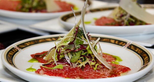 This is a collaboration by Old Homestead Steakhouse Executive Chef Oscar Martinez and Gunma Prefecture, Japan, Wagyu Farmer Katsuya Kato -- Prized Wagyu Sirloin Carpaccio, Bouquet of Greens, Herb Vinaigrette Fusion.