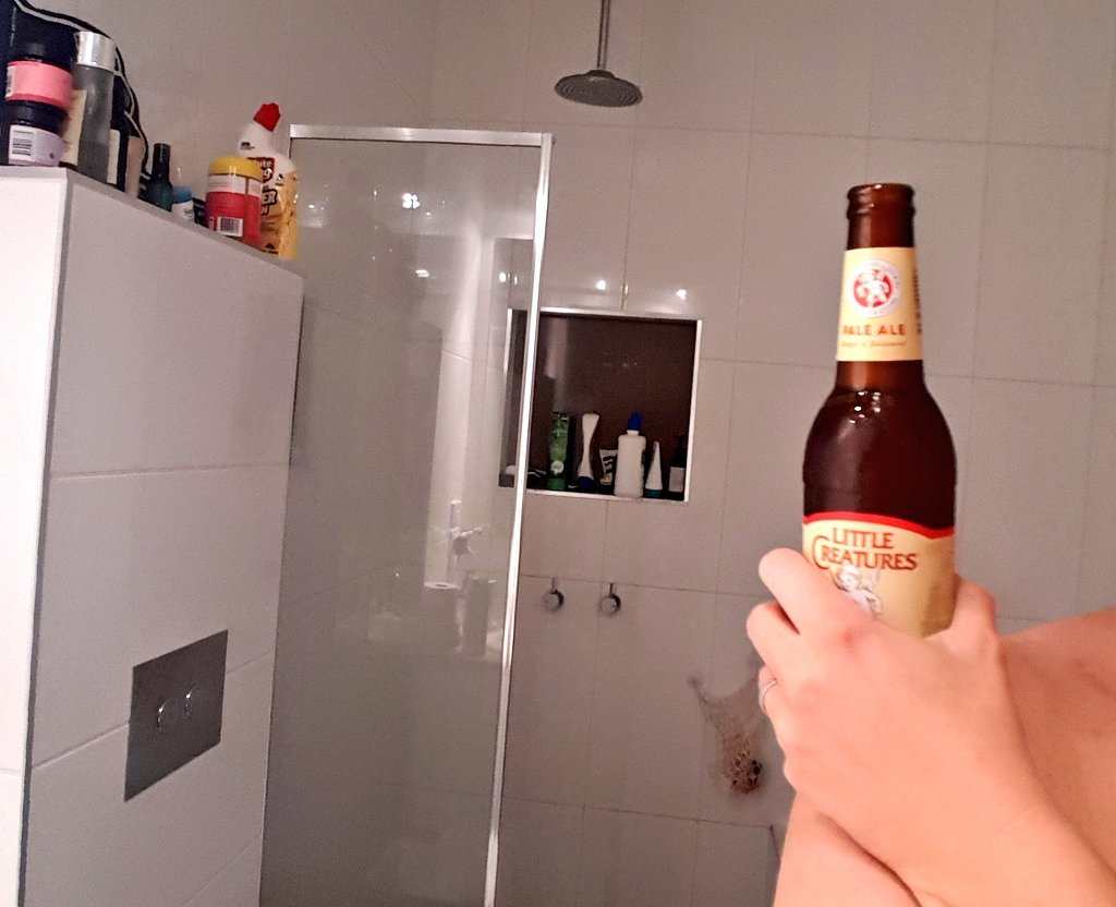 man's shower selfie holding beer