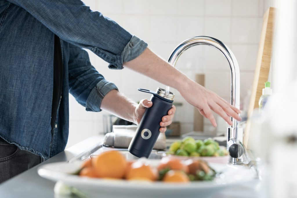 person filling water bottle at sink