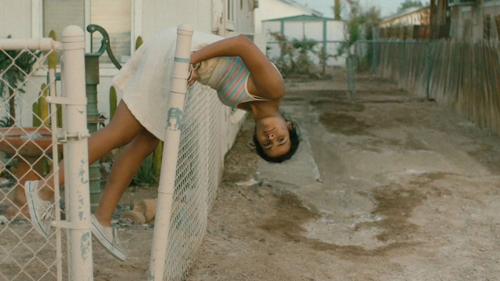 young girl hanging over fence