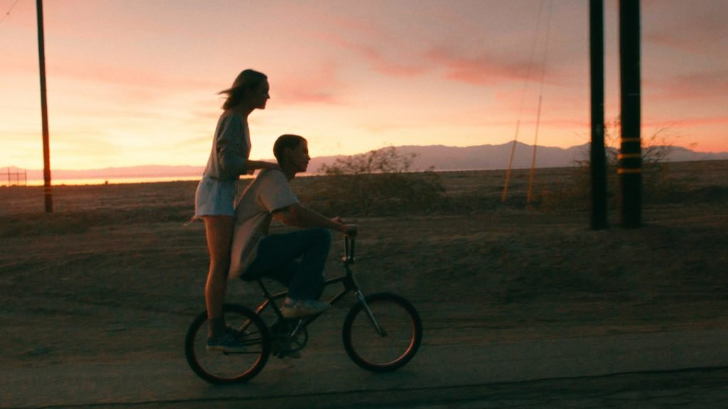 two teens on a bike at sunset