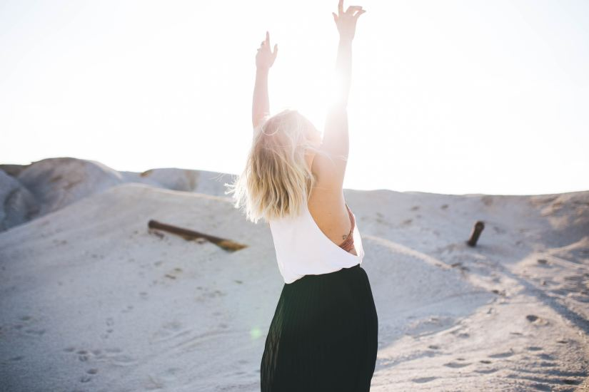 Girl standing on beach with her arms in the air.