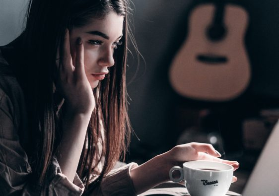 Girl sat at laptop with coffee looking sad