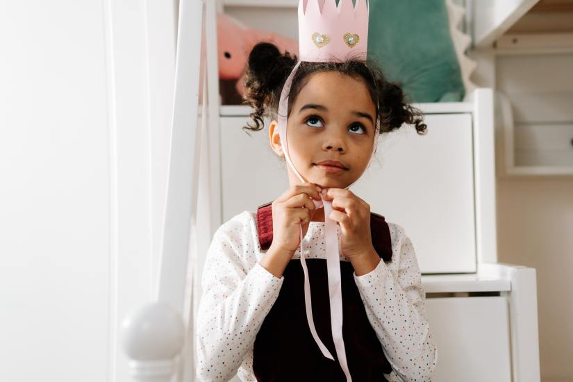 A girl putting on a pink crown.