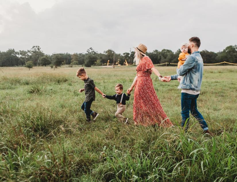 Woman holding mans hand, walking in field with family
