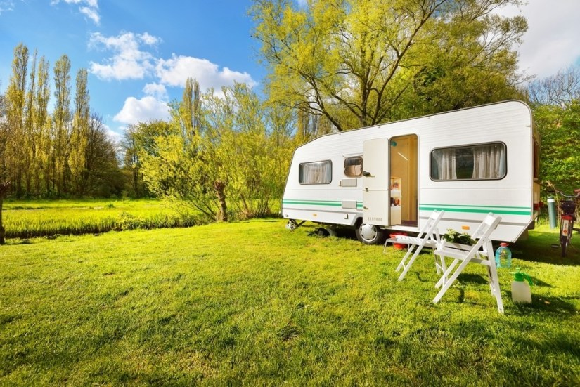Caravan in a beautiful field with picnic chairs