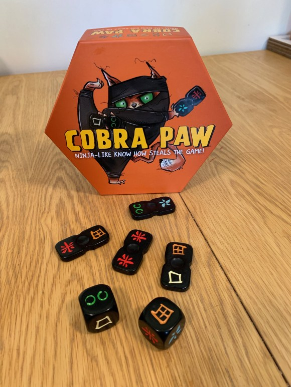 Cobra paw the game with tiles in front of the box