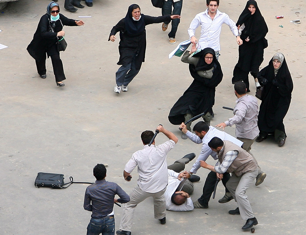 A supporter of defeated presidential candidate Mousavi is beaten by government security men as fellow supporters come to his aid during riots in Tehran, Iran, Sunday, June 14, 2009. (AP Photo) #