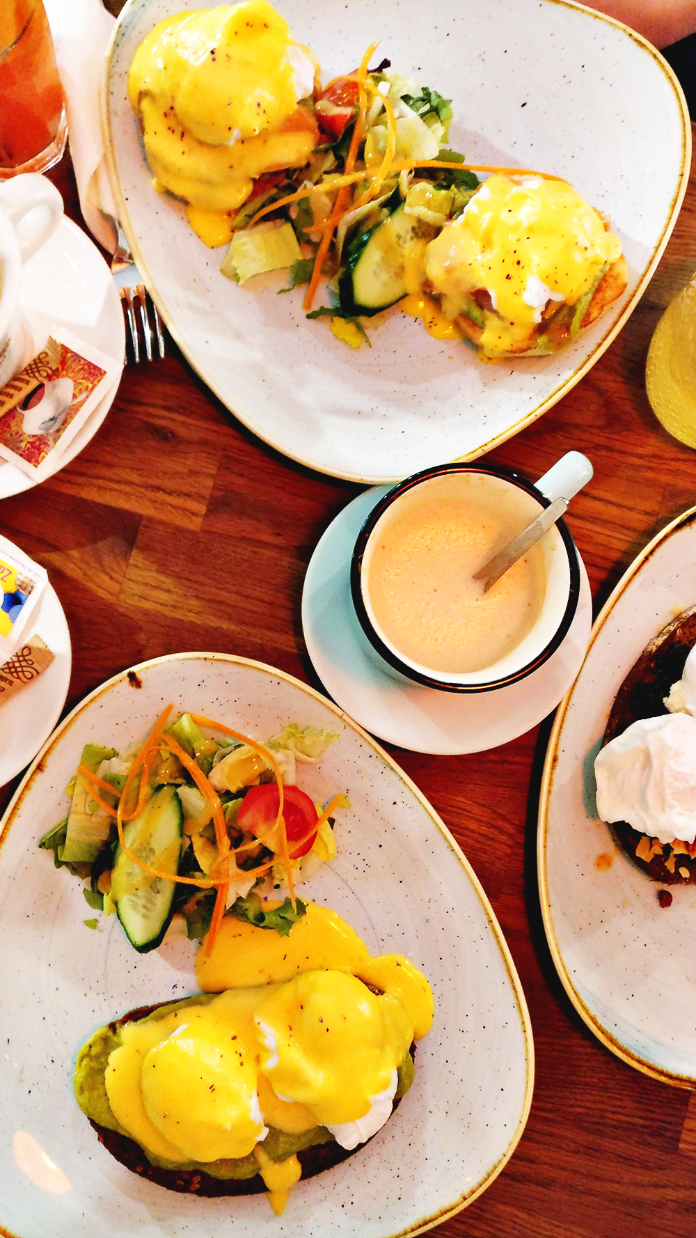 Poached eggs served with hollandaise sauce on rye bread with avocado cream in Kuglóf - Avocado toast lover's guide to Budapest, Hungary | Aliz's Wonderland #Budapest #Hungary #travel #avocadotoast #foodie #Budapestfoodguide