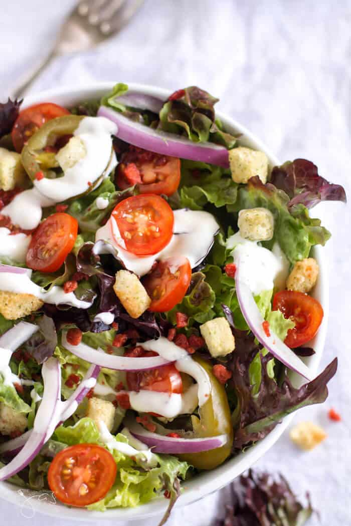 Red leaf lettuce, imitation bacon bits, red onions, cherry tomatoes and croutons are tossed with ranch salad dressing to make this simple copycat Sizzle Pie Rabbits salad