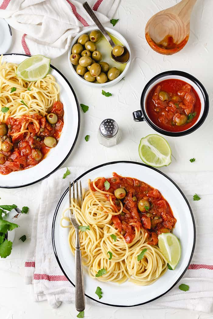 Spaghetti on two plates with a side of Veracruz sauce.