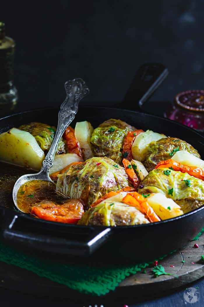 Skillet with Palestinian Stuffed Savoy Cabbage Rolls and a serving spoon