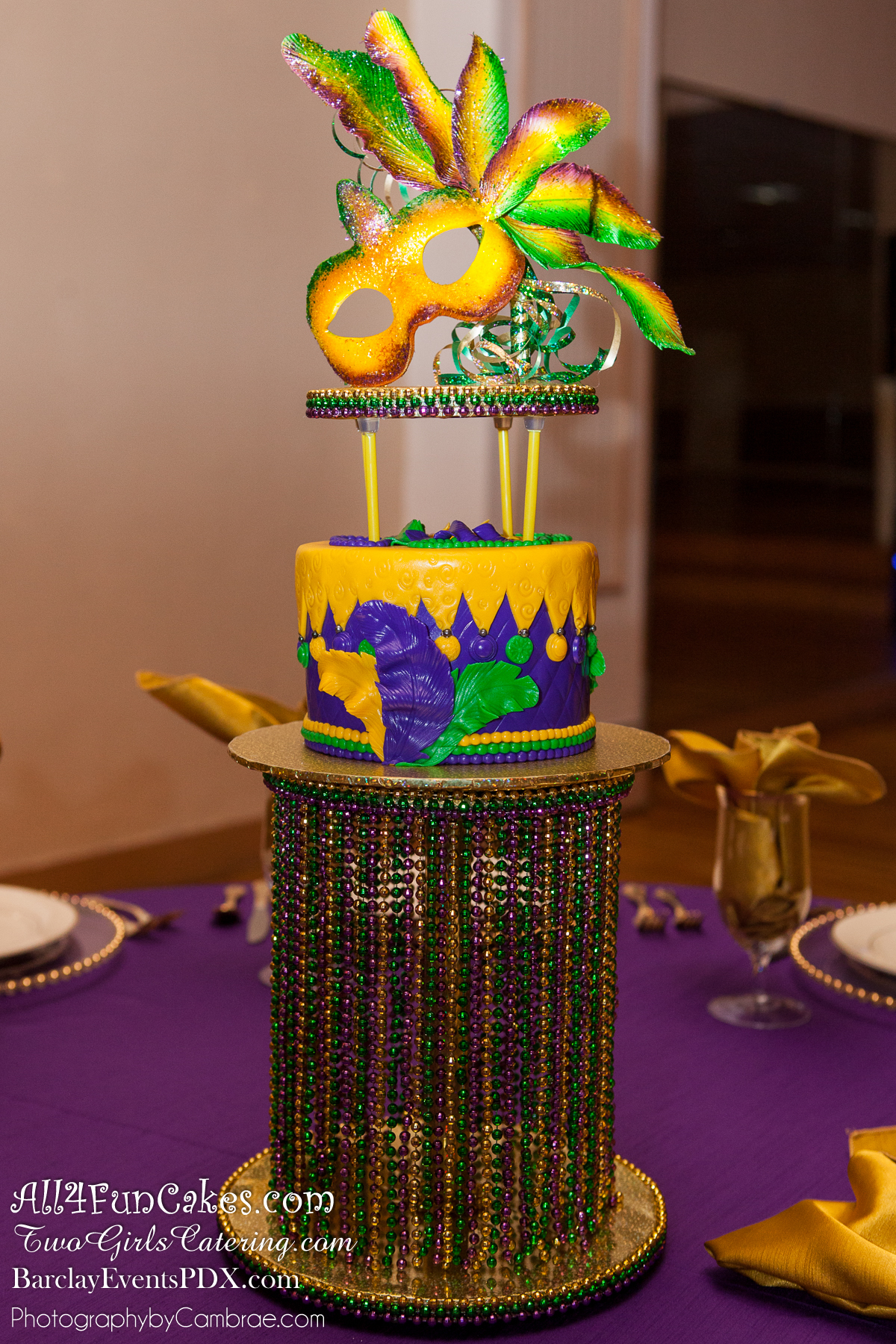 Pure Heaven White Chocolate Cake, Lemon Fruit Filling, White Chocolate Buttercream and Marshmallow Fondant. Hand-Crafted Pastillage Sugar Mask Topper and Custom Beaded Stand - Mardi Gras Cake Table - All4Fun Cakes LLC 2018