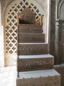 Intricately carved wooden steps and throne/chair all covered with dust.