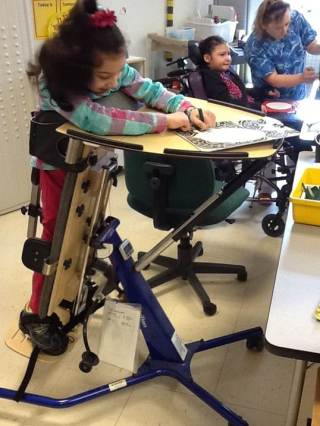 A prone stander helps Enji complete schoolwork