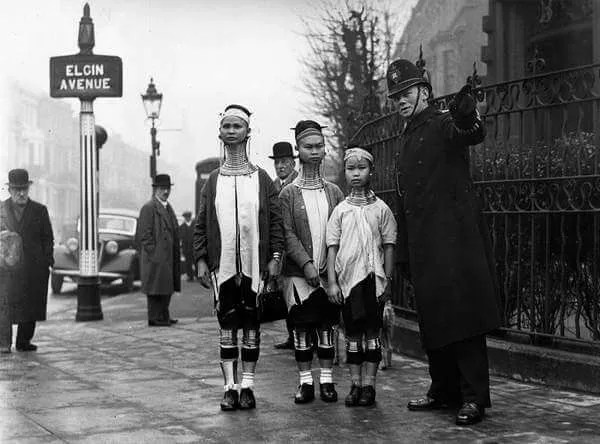 A policeman in London directing three giraffe necked women from Burma along Elgin Avenue, London. (Photo by General Photographic Agency/Getty Images)