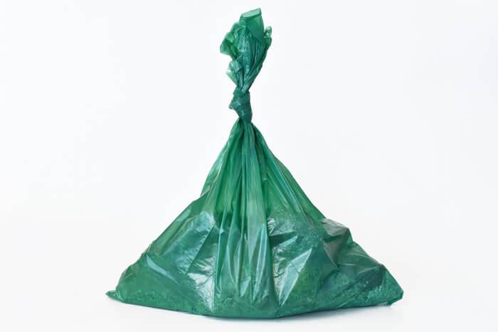 green trash bag full of cat poop and litter
