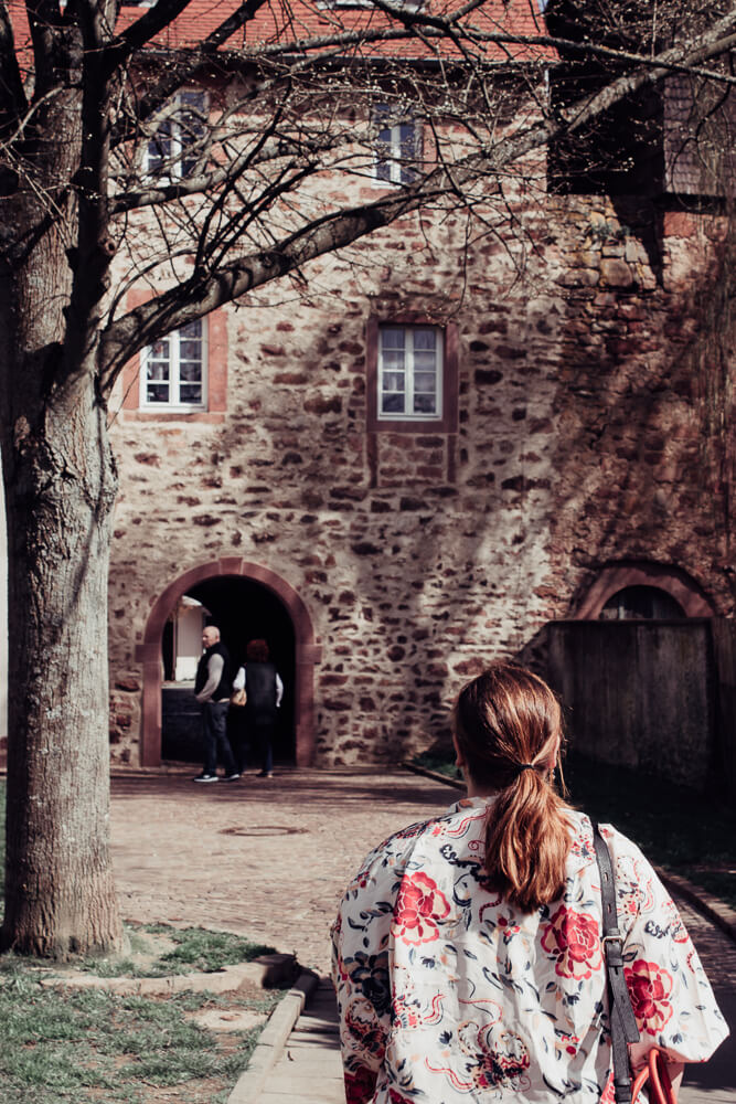 Woman with red hair walking through the city walls of Michelstadt