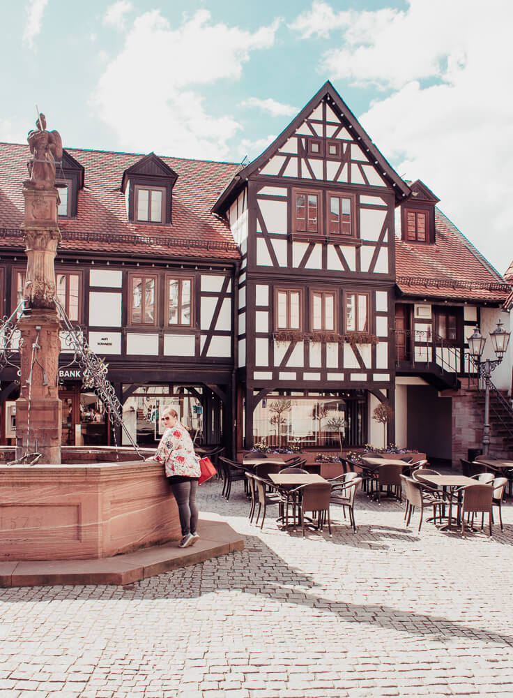 Woman looking at the ornate fountain, marktbrunnen, in the centre of Michelstadt town square