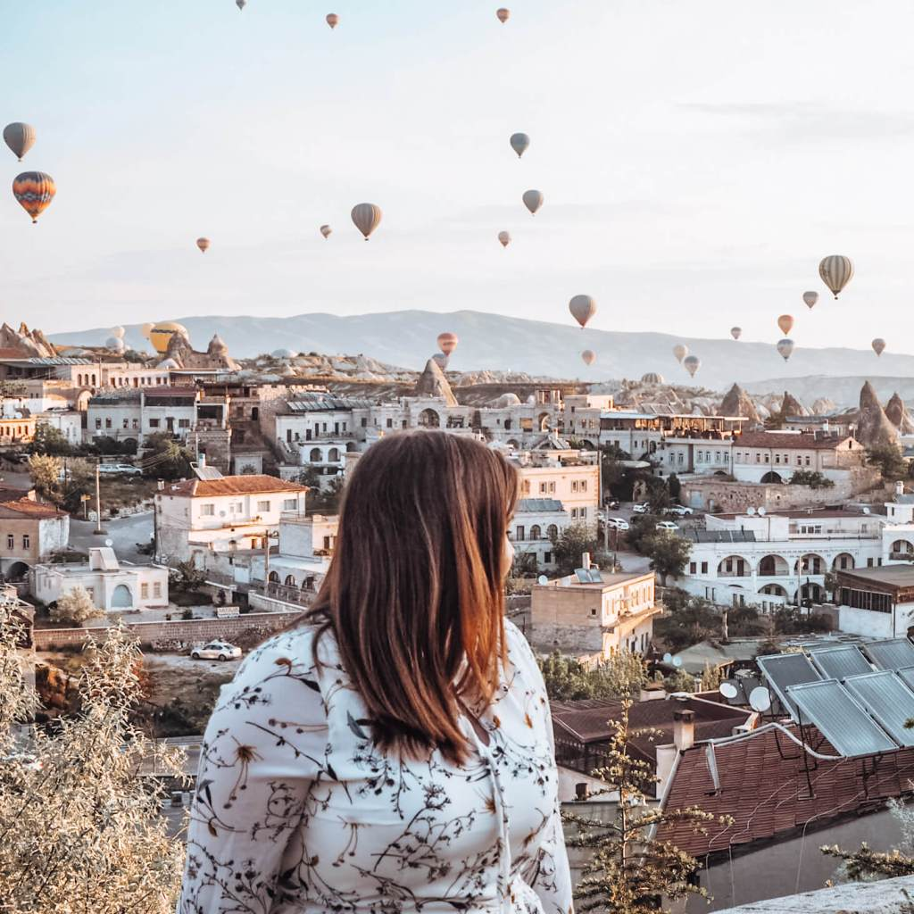 Women watching the hot air ballons rise over Goreme in Cappadocia Turkey