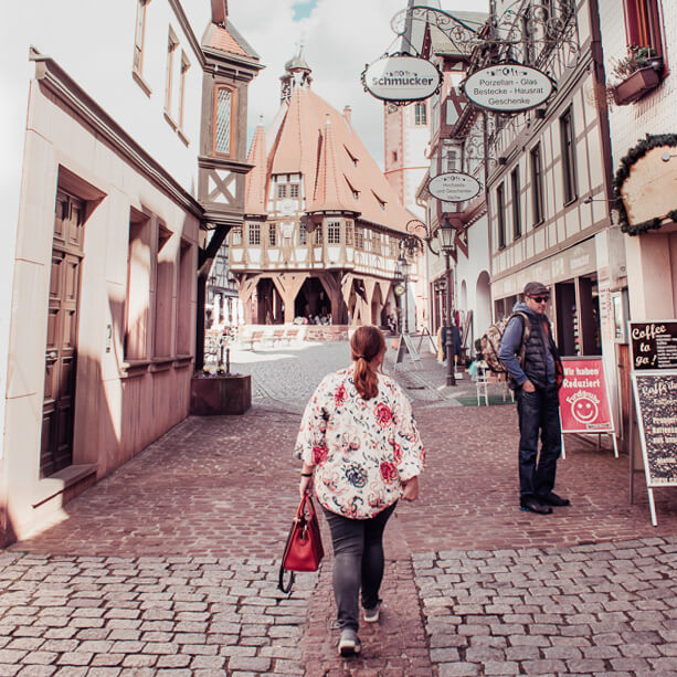 Woman wearing a floral top and jeans walking along the picturesque cobbled streets of Michelstadt in Odenwald Germany