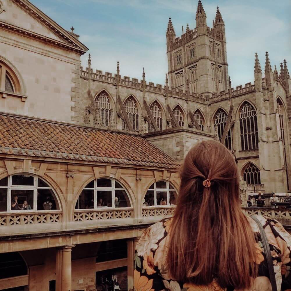 Woman with red hair looking at the Romn Baths in Bath city UK