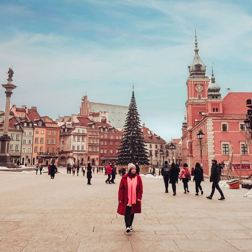 Woman wearing a red coat and pink scarf in Warsaw's main square at Christmas