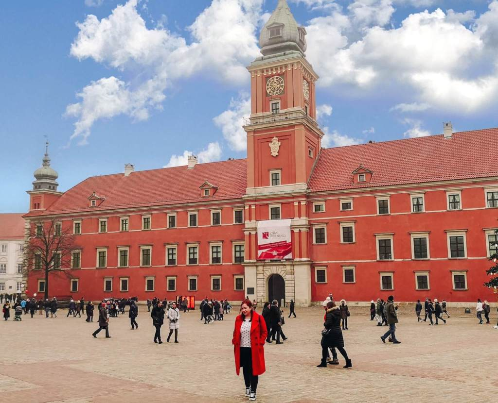 Woman in a red coat walking away from Warsaw Palace