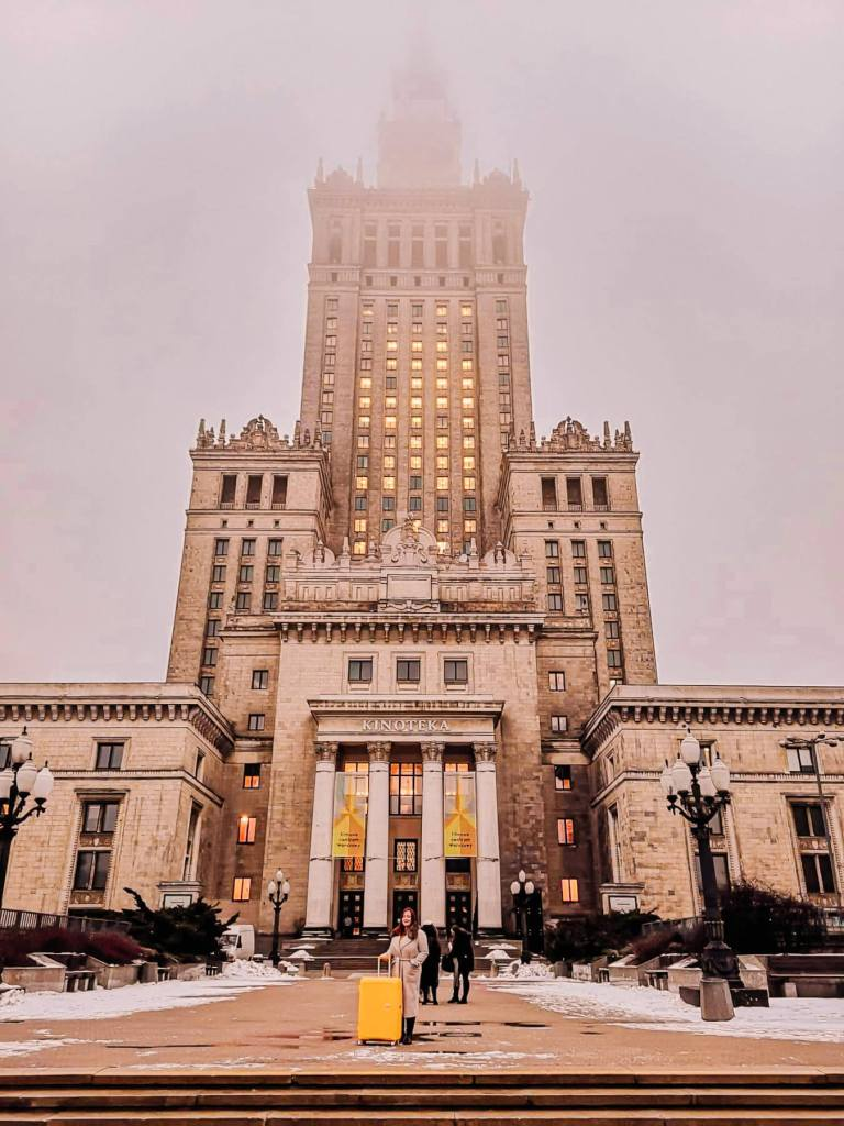Woman in a beige winter coat holding a yellow suitcase standing in from of The Palace of Science and Nature in Warsaw Poland
