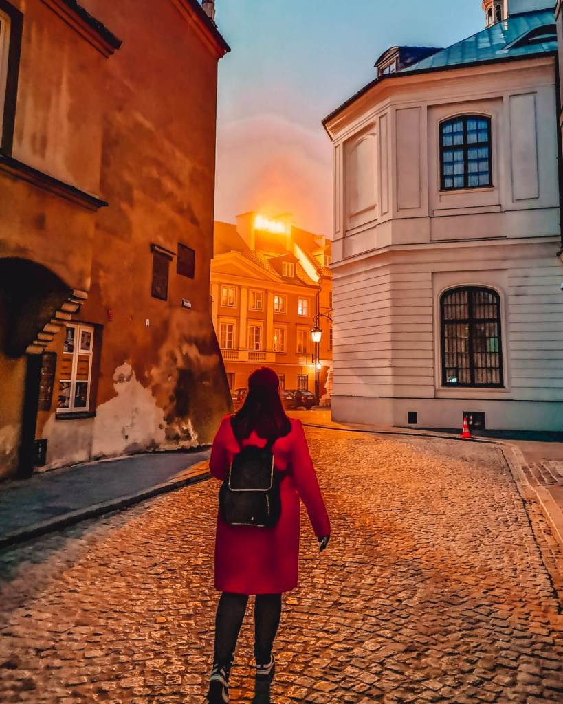 Woman walking along the cobbled alleyways of Warsaw at dusk