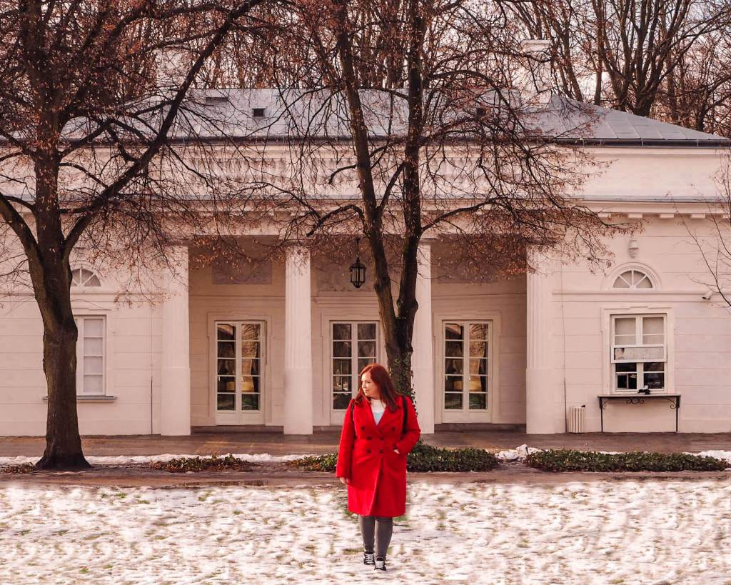 Woman in a red coat walking in the snow in a park in Warsaw